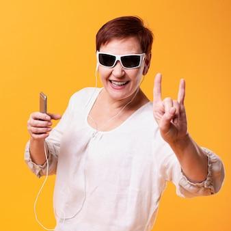 Gelukkige vrouw het luisteren muziek en het tonen van rotsteken