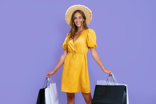 Gelukkige vrouw houdt boodschappentassen op kleurrijke achtergrond verkoopaankopen winkelen zwarte vrijdag