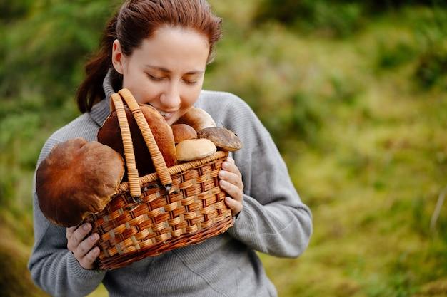 Gelukkige vrouw houdt een bosoogst in een rieten mand met paddestoelen gevonden horizontaal schot