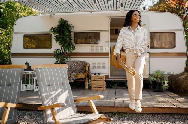 Gelukkige vrouw houdt gitaar in de buurt van de camper, kamperen in een aanhangwagen. stel reist op busje, vakanties op camper