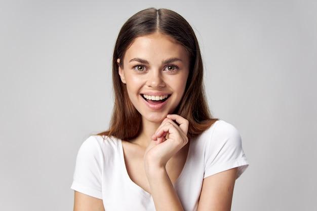 Gelukkige vrouw houdt haar hand in de buurt van haar gezicht en lacht op een lichte achtergrond