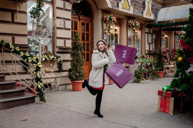 Gelukkige vrouw houdt papieren zakken met symbool van verkoop in de winkels met verkoop met kerstmis