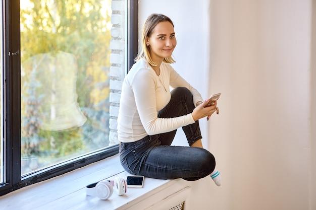 Gelukkige vrouw houdt telefoon vast terwijl ze thuis op de vensterbank zit
