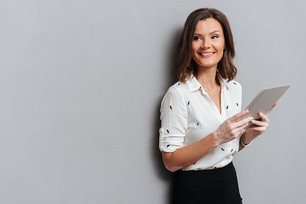 Gelukkige vrouw in bedrijfskleren die dichtbij de muur met tabletcomputer stellen op grijs