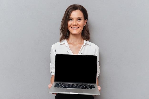 Gelukkige vrouw in bedrijfskleren die het lege laptop computerscherm op grijs tonen
