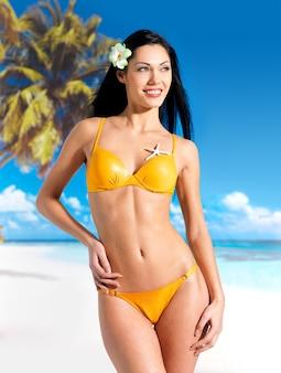 Gelukkige vrouw in bikini op strand. kust als achtergrond