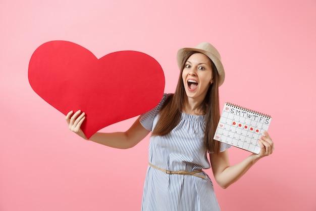 Gelukkige vrouw in blauwe jurk zomer hoed met leeg leeg groot rood hart, vrouwelijke perioden kalender, menstruatie dagen geïsoleerd op de achtergrond controleren. medische gezondheidszorg gynaecologische concept. ruimte kopiëren