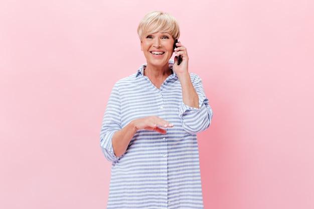 Gelukkige vrouw in blauwe outfit praten over de telefoon op geïsoleerde achtergrond