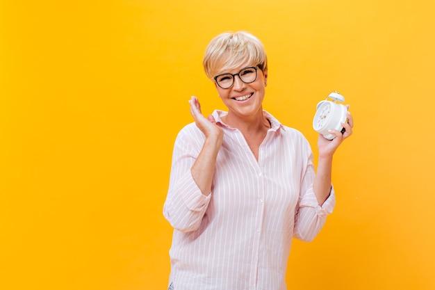 Gelukkige vrouw in brillen en roze outfit vormt met wekker op oranje achtergrond