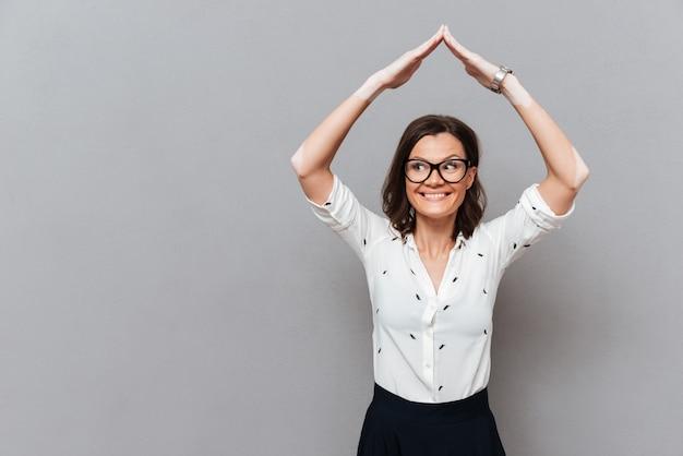Gelukkige vrouw in brillen en zakelijke kleding verbergen onder handen zoals huis op grijs