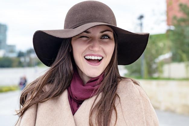 Gelukkige vrouw in bruine hoed en beige jas, knipogen met één oog naar de camera en glimlacht breed met witte tanden. e.