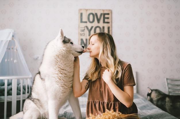 Gelukkige vrouw in bruine jurk zittend op bed en schattige husky puppy knuffelen.