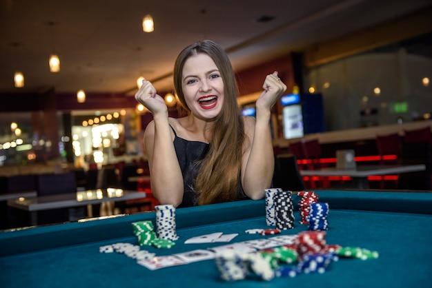 Gelukkige vrouw in casino met pookspaanders en kaarten