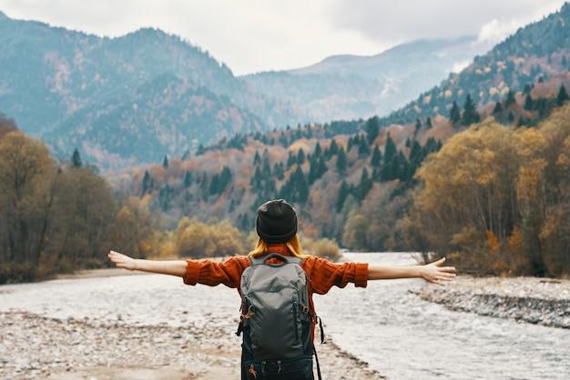 Gelukkige vrouw in de bergen reist in de buurt van de rivier in de natuur en hief haar handen op