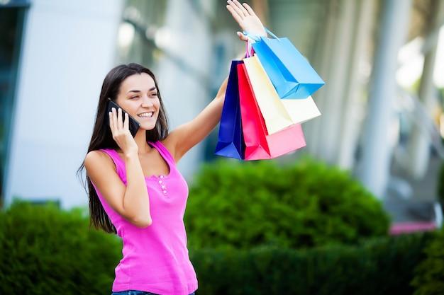 Gelukkige vrouw in de buurt van winkelcentrum houden geschenk zakken en bellen