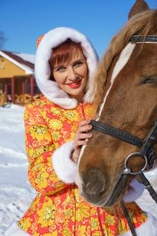 Gelukkige vrouw in de winter met een paard op straat