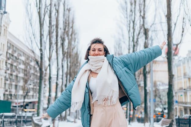 Gelukkige vrouw in de winter op besneeuwde stadssteeg