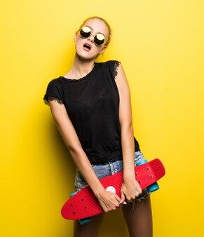 Gelukkige vrouw in denimkleding en zonnebril met skateboard die pret hebben en de camera over gele achtergrond bekijken