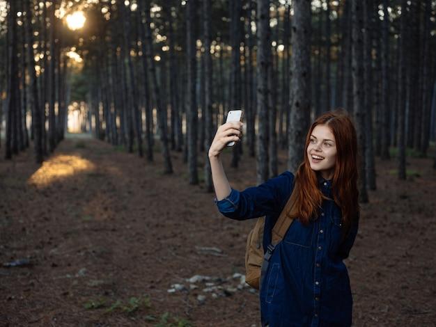Gelukkige vrouw in dennenbos met mobiele telefoon navigator toerisme model