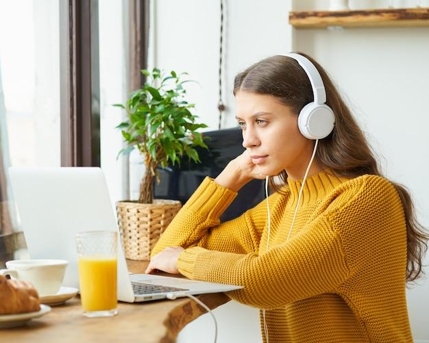 Gelukkige vrouw in draadloze hoofdtelefoons die online studeren, laptop gebruiken en ontbijten