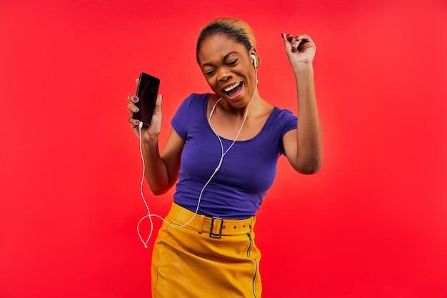Gelukkige vrouw in een blauw t-shirt en in een gele rok met haar verzameld in een knot met een telefoon