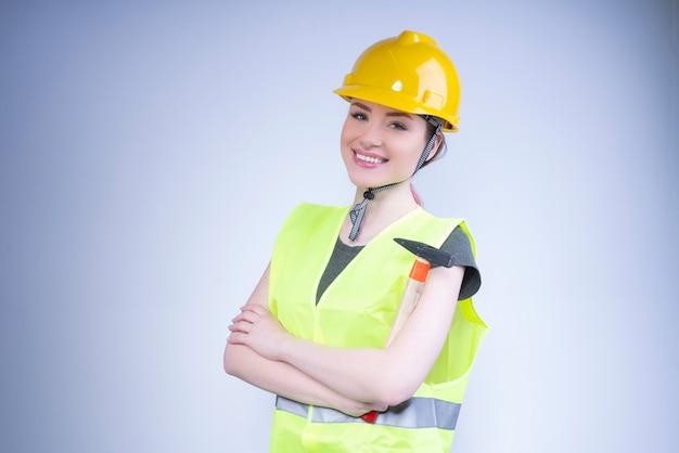 Gelukkige vrouw in een gele helm en een werkvest