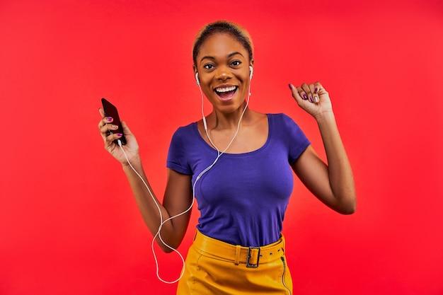 Gelukkige vrouw in een gele rok in een blauw t-shirt en met haar verzameld in een knot met een telefoon