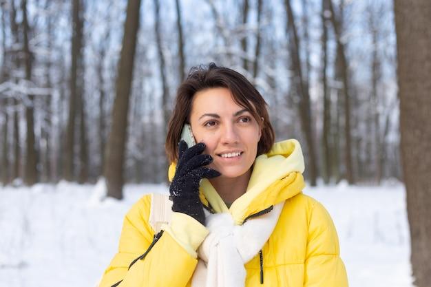 Gelukkige vrouw in een goed humeur wandelingen door het besneeuwde winterbos en vrolijk chatten aan de telefoon, genieten van tijd buiten in het park
