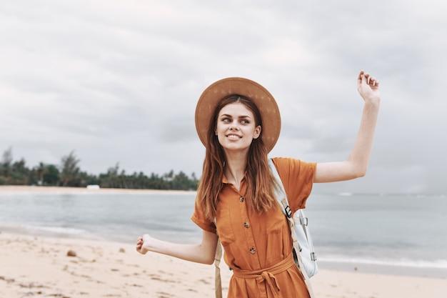Gelukkige vrouw in een hoed reist op een eiland