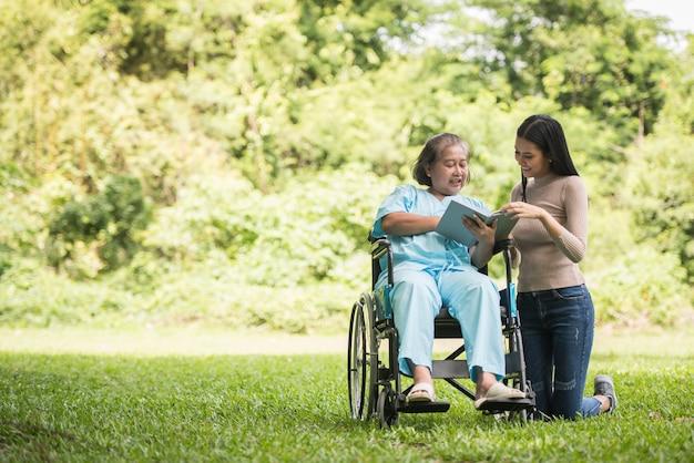 Gelukkige vrouw in een rolstoel die een boek met haar dochter leest bij het park