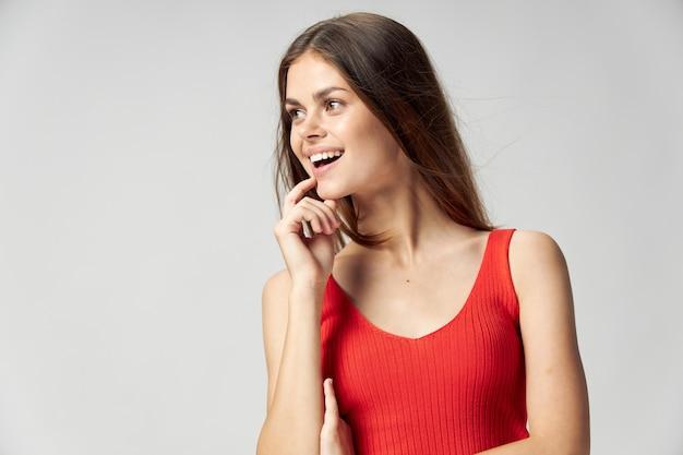 Gelukkige vrouw in een rood t-shirt raakt haar gezicht met haar hand en kijkt naar de zijkant op een licht