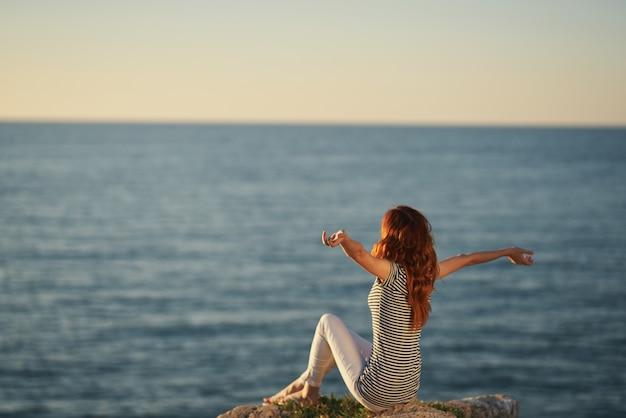 Gelukkige vrouw in een t-shirt en broek bij de zee hief haar handen op