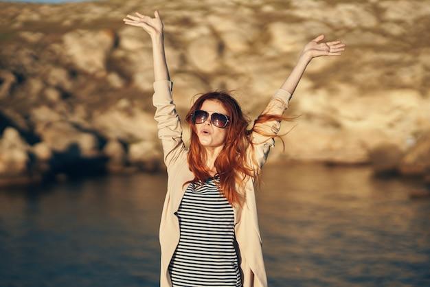 Gelukkige vrouw in een t-shirt houdt haar handen boven haar hoofd in de bergen in de natuur in de buurt van de rivier