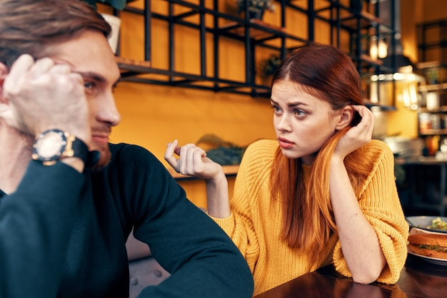 Gelukkige vrouw in een trui gebaren met haar handen leuke emoties en een man in een trui zit in een café