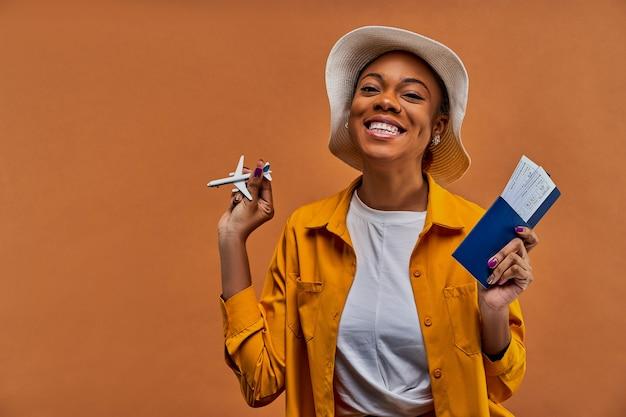 Gelukkige vrouw in een witte hoed in geel overhemd glimlacht naar de camera met een speelgoedvliegtuig met een paspoort met kaartjes in handen. reis concept