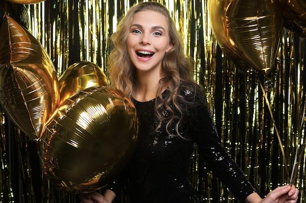 Gelukkige vrouw in feestelijke outfit met gouden ballonnen.