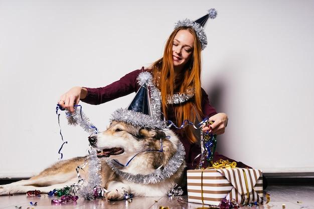 Gelukkige vrouw in feestelijke pet zit naast grote hond