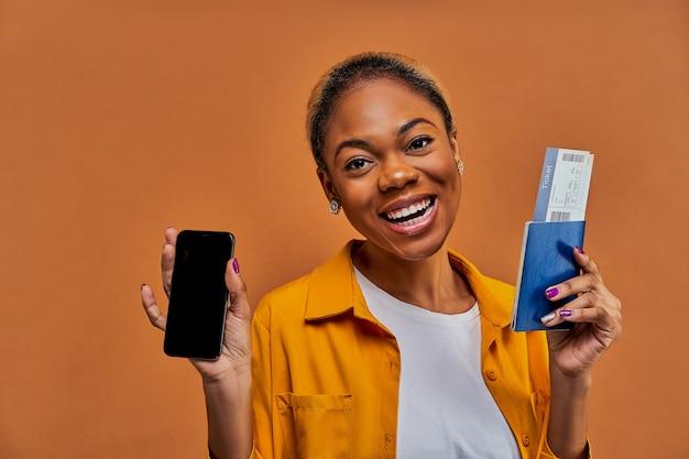 Gelukkige vrouw in geel overhemd glimlacht naar de camera en toont een smartphone met een paspoort met kaartjes in handen. reis concept