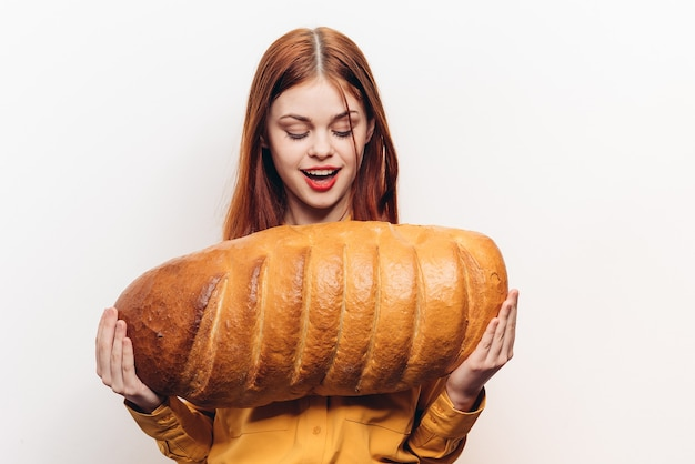 Gelukkige vrouw in geel overhemd heeft een groot brood in haar handen en glimlacht.