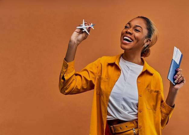 Gelukkige vrouw in geel overhemd met een speelgoedvliegtuig met een paspoort met kaartjes in handen. reis concept