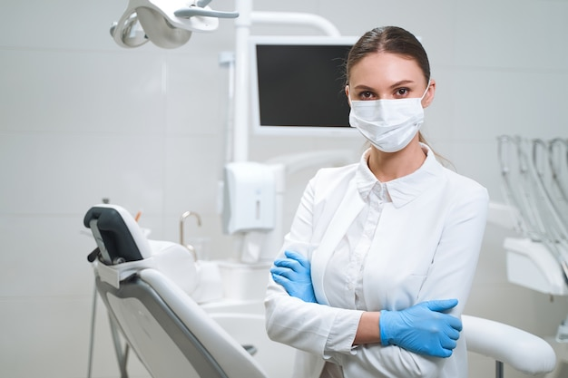 Gelukkige vrouw in gekke uniforme en steriele handschoenen en masker wacht op patiënten in een modern kantoor.