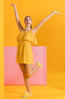 Gelukkige vrouw in gele jurk