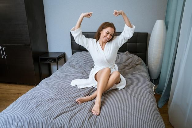 Gelukkige vrouw in gewaad in de ochtend die zich uitstrekt op bed thuis
