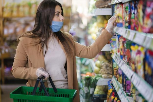 Gelukkige vrouw in gezichtsmasker die verse kerstomaatjes neemt terwijl hij bij boodschappen in de supermarkt staat
