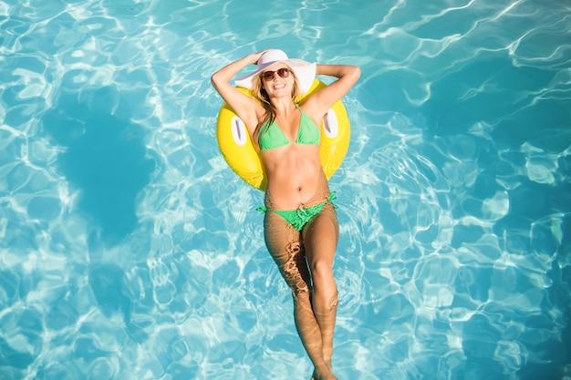 Gelukkige vrouw in groene bikini die op opblaasbare buis in zwembad drijft