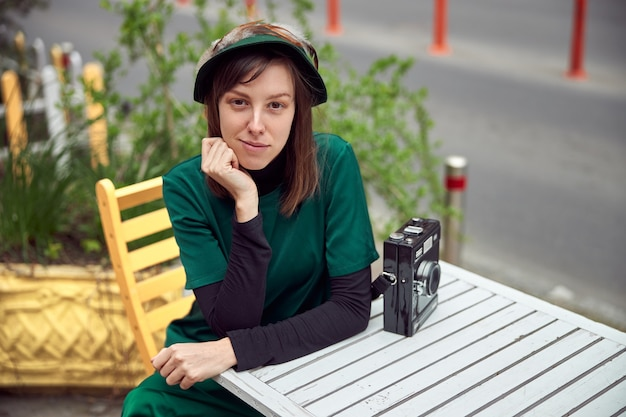 Gelukkige vrouw in groene jurk in stedelijke stad zit in de buurt van café