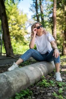 Gelukkige vrouw in het bos geniet van vrije zomertijd boven het bosoppervlak