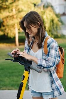 Gelukkige vrouw in het park betaalt voor haar elektrische scooter met een telefoon-app