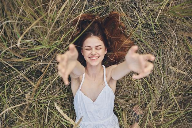 Gelukkige vrouw in hooiberg strekt zich uit handen omhoog en bijgesneden weergave.