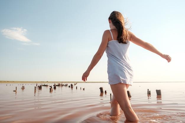 Gelukkige vrouw in jurk die in het meer loopt jonge vrouw geniet van de kust van de rode zee dromerig meisje wandelen